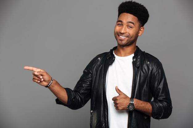 Feliz joven afroamericano en chaqueta de cuero apuntando con un dedo mientras muestra el pulgar hacia arriba gesto, mirando