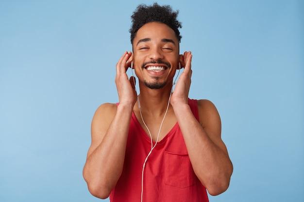 Feliz joven afroamericano de piel oscura se siente genial, cierra los ojos y disfruta con la música, usa auriculares, aislado.