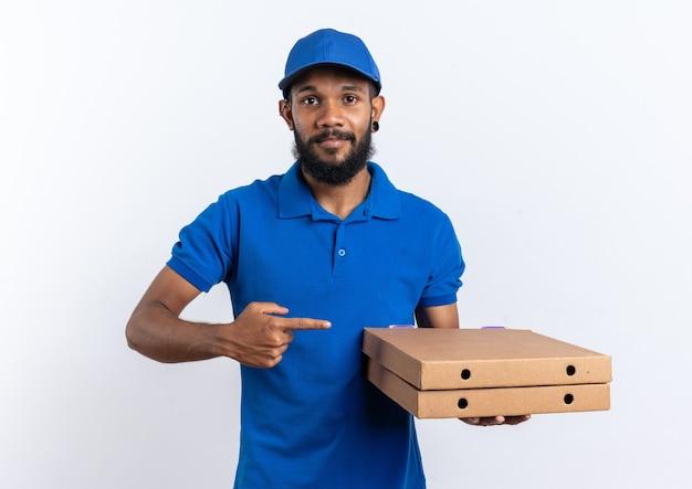 Feliz joven afroamericano repartidor sosteniendo y apuntando a cajas de pizza aisladas sobre fondo blanco con espacio de copia