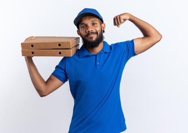 Feliz joven afroamericano repartidor sosteniendo cajas de pizza y tensando bíceps aislado sobre fondo blanco con espacio de copia