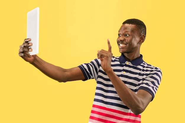 Feliz joven afroamericano con tableta aislado sobre fondo amarillo estudio, expresión facial. hermoso retrato masculino de media longitud. concepto de emociones humanas, expresión facial.