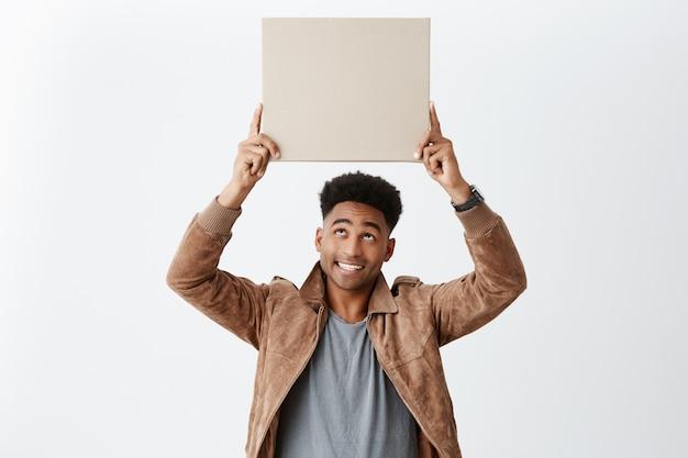 Feliz joven alegre hombre de piel oscura con peinado afro en ropa hipster elegante con cartón escuchar, mirando al revés con sonrisa y expresión satisfecha. emociones positivas