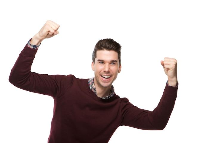 Feliz joven animando con los brazos alzados