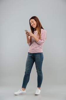 Feliz joven asiática chateando por teléfono