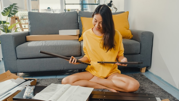 Feliz joven asiática desembalaje de la caja y leyendo las instrucciones para montar muebles nuevos