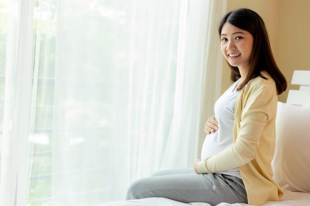 Feliz joven asiática embarazada sosteniendo el vientre sonriendo