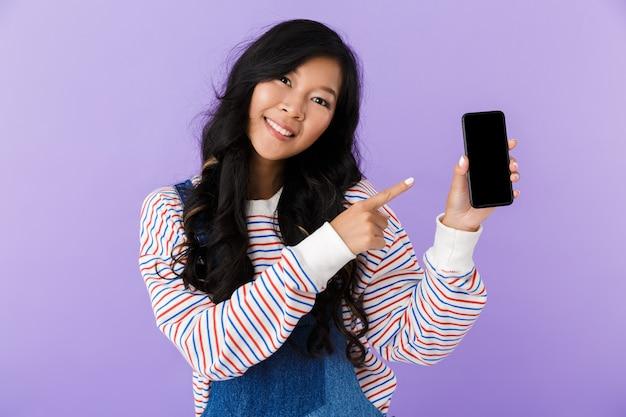 Feliz joven asiática hermosa mujer atractiva posando aislada en el interior apuntando a la pantalla del teléfono móvil