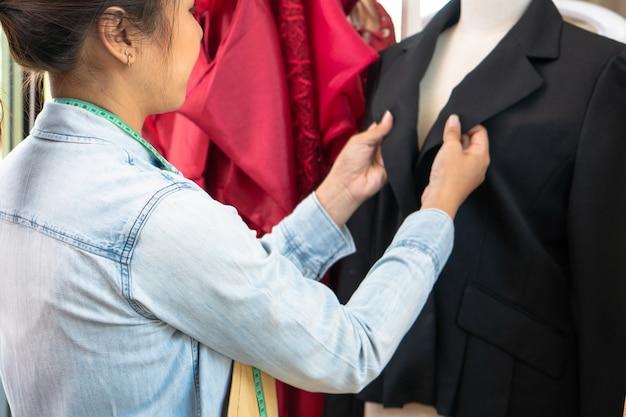 Feliz joven asiática modista diseñador de moda está comprobando la finalización de un traje y vestido en una sala de exposición. concepto de éxito joven emprendedor en el negocio de la moda.