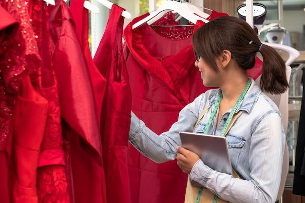Feliz joven asiática modista diseñador de moda está comprobando la finalización de un traje y vestido y sosteniendo la tableta en una sala de exposición.
