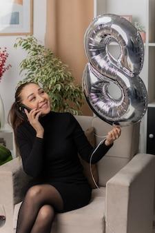 Feliz joven asiática vestida de negro sentada en una silla con globo en forma de número ocho sonriendo alegremente hablando por teléfono móvil en la sala de estar luminosa celebrando el día internacional de la mujer