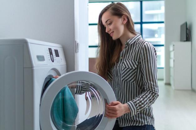 Feliz joven atractiva cargando ropa en la lavadora en casa