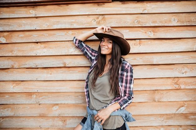 Feliz joven atractiva vaquera en camisa a cuadros y sombrero de pie y sonriendo sobre fondo de madera