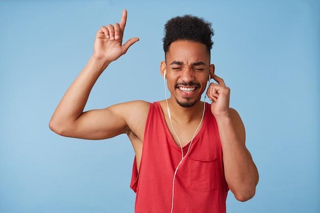 Feliz Joven Atractivo De Piel Oscura Escucha Buena Música Viste Una Camiseta Roja Sostiene El Auricular Con La Mano Izquierda Cierra Los Ojos Canta Y Baila En Voz Alta Se Pone De