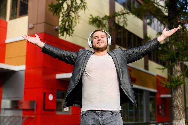 Feliz joven con auriculares levantando sus manos en los lados