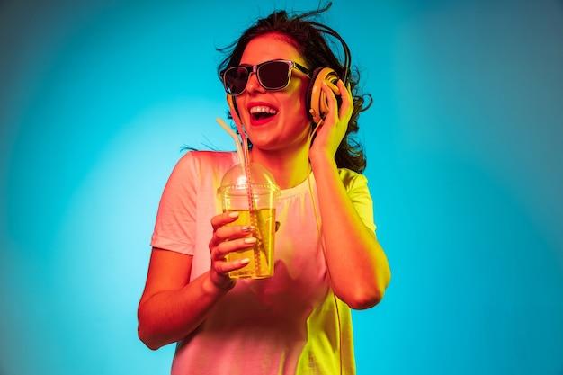 Feliz joven bailando y sonriendo en auriculares sobre moderno estudio de neón azul