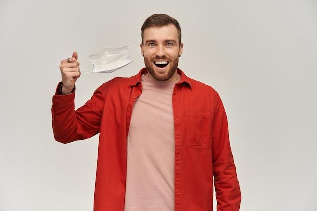 Feliz joven con barba en camisa roja quitándose la mascarilla higiénica para prevenir infecciones y respirar más profundamente sobre la pared blanca