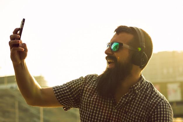 Feliz joven con barba larga tomando una selfie con su teléfono en la calle