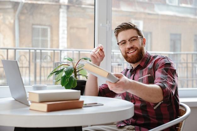 Feliz joven barbudo mostrando libro