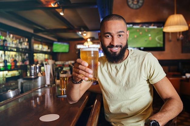 Feliz joven barbudo sentado y bebiendo cerveza en el bar