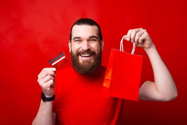 Feliz joven barbudo sosteniendo su tarjeta de crédito y bolsa roja, compras en línea