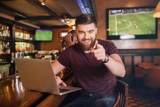 Feliz joven barbudo usando laptop y apuntando a usted en pub