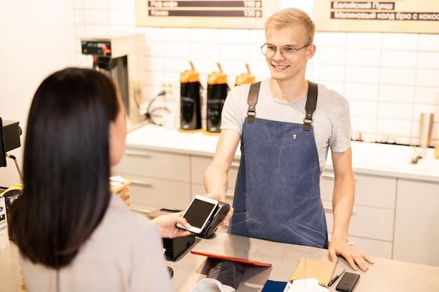 Feliz joven barista mirando al cliente que paga por la bebida mientras sostiene el teléfono inteligente sobre la máquina de pago electrónico