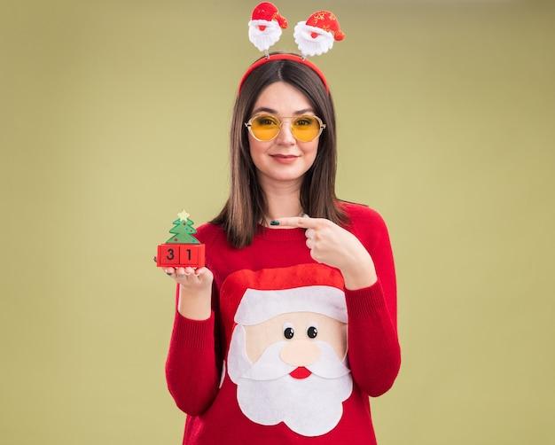 Feliz joven bastante caucásica vistiendo suéter de santa claus y diadema con gafas sosteniendo y apuntando al juguete del árbol de navidad con fecha