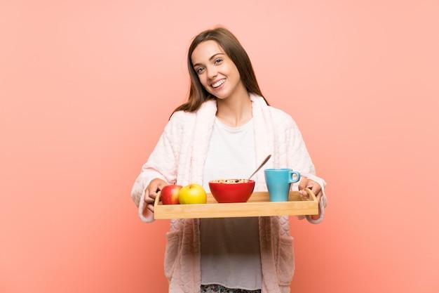 Feliz joven en bata sobre pared rosa con desayuno