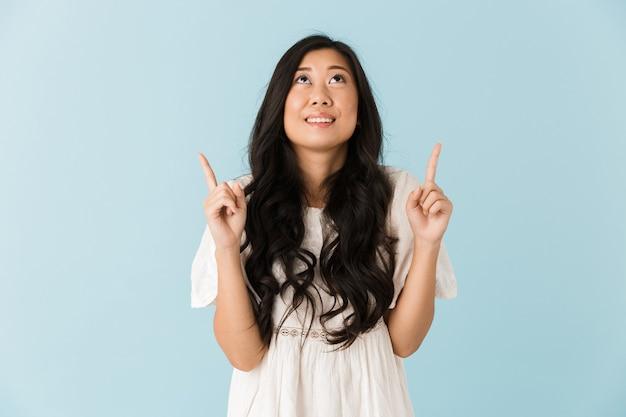 Feliz joven bella mujer asiática posando aislada sobre pared azul apuntando