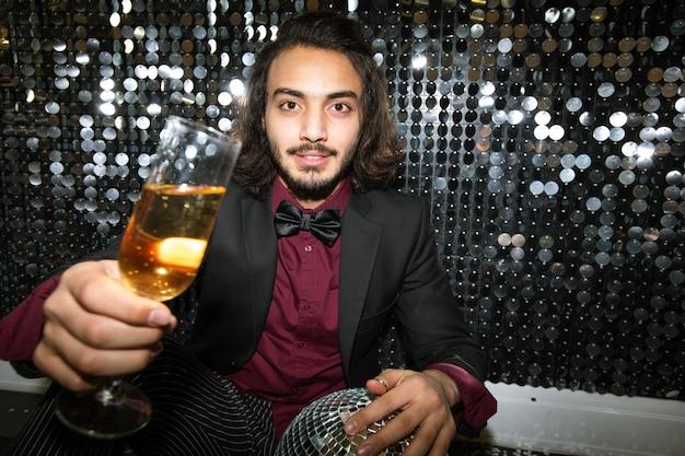 Feliz joven bien vestido animando con flauta de champán mientras está sentado en el suelo junto a la pared brillante en la fiesta