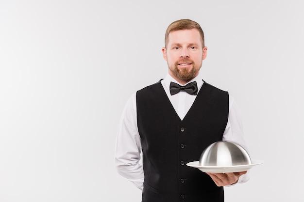 Feliz joven camarero en chaleco y pajarita sosteniendo cloche con comida mientras está de pie frente a la cámara de forma aislada