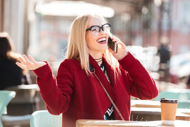Feliz joven caucásica hablando por teléfono tomando café.