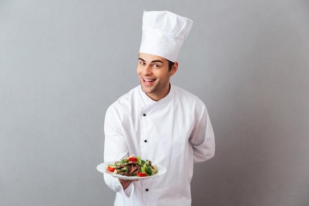 Feliz joven cocinero en uniforme con ensalada.
