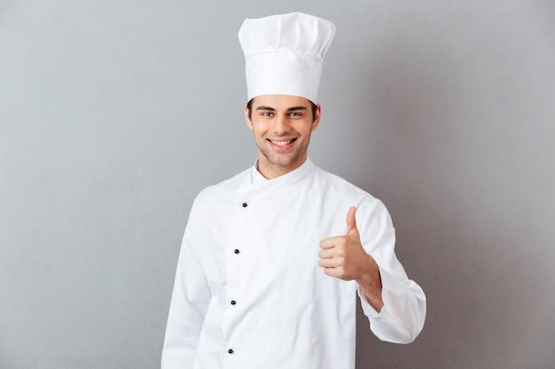 Feliz joven cocinero en uniforme mostrando los pulgares para arriba.