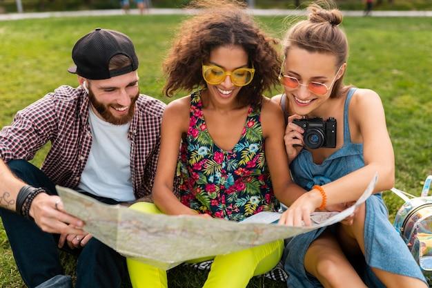 Feliz joven compañía de amigos sentados en el parque viajando mirando en el mapa de turismo, hombres y mujeres divirtiéndose juntos