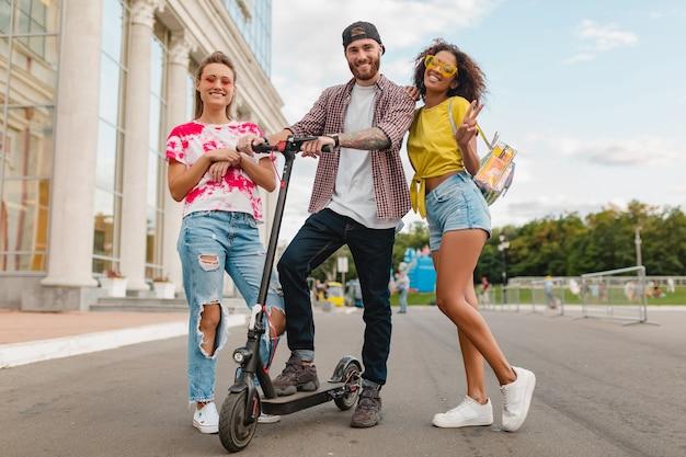 Feliz joven compañía de amigos sonrientes caminando en la calle con patinete eléctrico, hombre y mujer divirtiéndose juntos