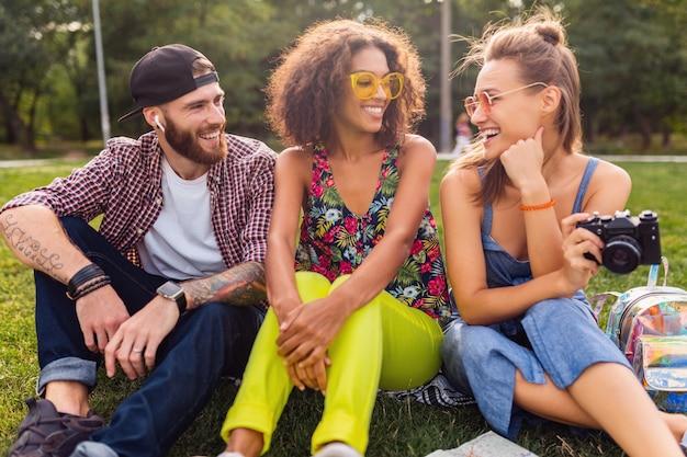 Feliz joven compañía de amigos sonrientes hablando sentado en el parque, hombres y mujeres divirtiéndose juntos, estilo de moda hipster de verano colorido, viajando con cámara
