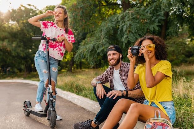 Feliz joven compañía de amigos sonrientes sentados en el parque sobre el césped con patinete eléctrico, hombre y mujer divirtiéndose juntos