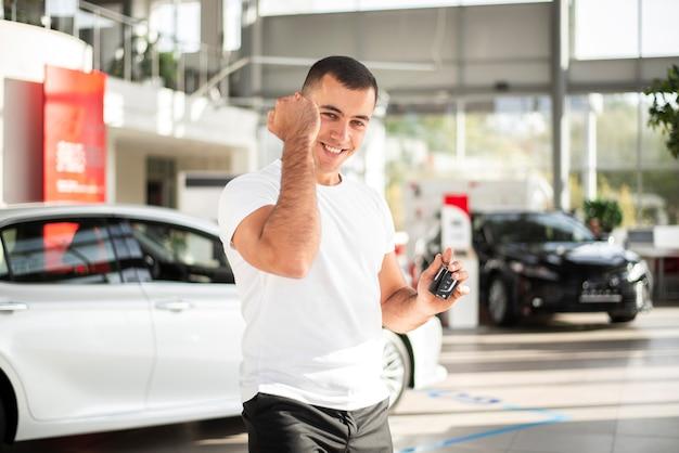 Feliz joven en concesionario de automóviles