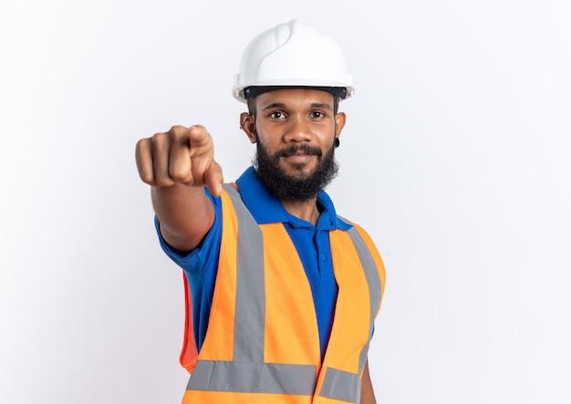 Feliz joven constructor afroamericano en uniforme con casco de seguridad apuntando a la cámara aislada sobre fondo blanco con espacio de copia