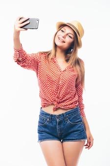 Feliz joven coqueteando tomando fotografías de sí misma a través del teléfono celular, sobre fondo blanco.