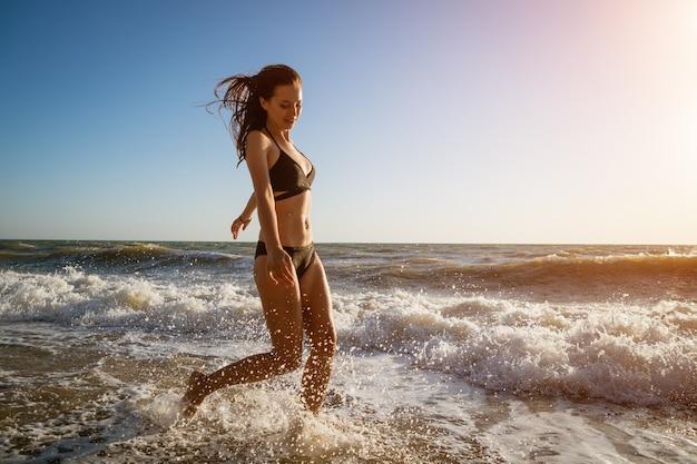 Feliz joven corre a lo largo de la playa en traje de baño negro en un día soleado de verano