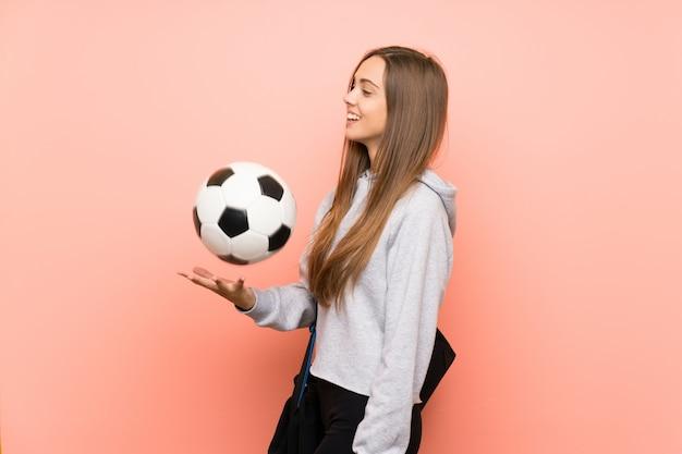 Feliz joven deporte mujer rosa sosteniendo un balón de fútbol