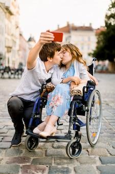 Feliz joven discapacitada en silla de ruedas besándose con su joven novio y sonriendo mientras toma selfie con él en la ciudad