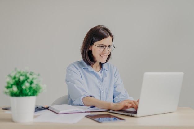 Feliz joven empresaria en camisa casual y grandes gafas redondas analiza la información en la computadora portátil