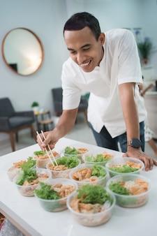 Feliz joven empresario de alimentos preparando su producto en casa
