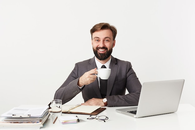 Feliz joven empresario barbudo con cabello castaño corto que trabaja en la oficina moderna, tomando una taza de café antes de la reunión, sonriendo con alegría al frente mientras está sentado sobre una pared blanca