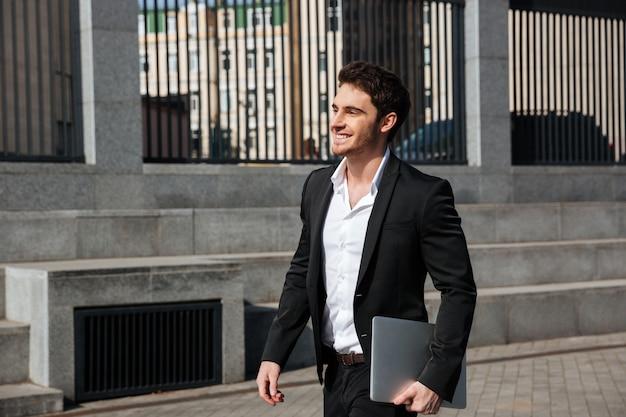 Feliz joven empresario caminando al aire libre