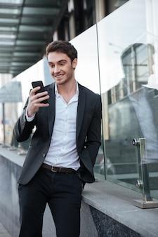 Feliz joven empresario caminando cerca del centro de negocios.