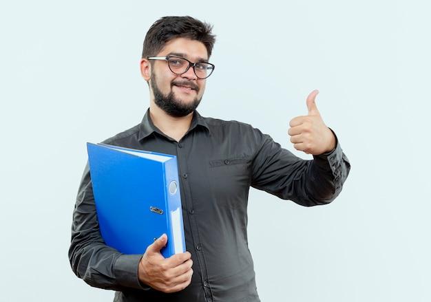 Feliz joven empresario con gafas sosteniendo la carpeta con el pulgar hacia arriba aislado sobre fondo blanco.